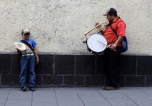 Un hombre toca la trompeta y la batería mientras su hijo espera por peatones a que le entreguen monedas en una vereda cerca de la plaza de Zocalo, 26 de agosto de 2013. La inflación en México a tasa anual se aceleró en la primera mitad de junio a un 3.71 por ciento, ligeramente menor a lo esperado por analistas, dijo el martes el instituto nacional de estadísticas, INEGI. REUTERS/Henry Romero