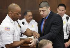 A court officer removes handcuffs from former New England Patriots football player AaronHernandez during a hearing in Suffolk Superior Court before a hearing in Boston, Massachusetts, June 24, 2014. REUTERS/Steven Senne/Pool