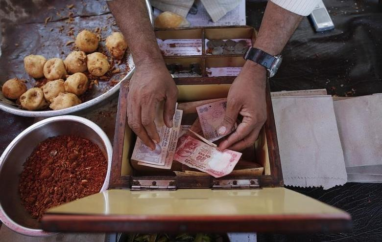 A streetside restaurant owner keeps money received from a customer in Mumbai December 5, 2013. REUTERS/Danish Siddiqui/Files