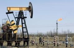 """Сотрудник Роснефти у станка-качалки на невятном месторождении Юганскнефтегаза близ Нефтеюганска 26 апреля 2006 года. Ключевые ведомства, регулирующие налоговый климат в топливно-энергетическом комплексе - Минфин и Минэнерго - согласовали режим """"большого налогового маневра"""" на три года, в соответствии с которым ставка НДПИ на нефть в 2015 году вырастет на 57 процентов к 2014 году до 775 рублей за тонну. REUTERS/Sergei Karpukhin"""