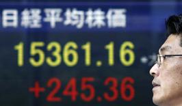 Un peatón camina frente a una pantalla electrónica que muestra el nikkei japonés fuera de una bolsa de valores en Tokio, 24 de junio de 2014. El índice Nikkei de la bolsa de Tokio cayó el miércoles a un mínimo en una semana luego de que los inversores recogieron ganancias de los últimos repuntes, mientras que la estrategia ampliamente esperada de crecimiento del Gobierno recibió una reacción apagada del mercado. REUTERS/Yuya Shino