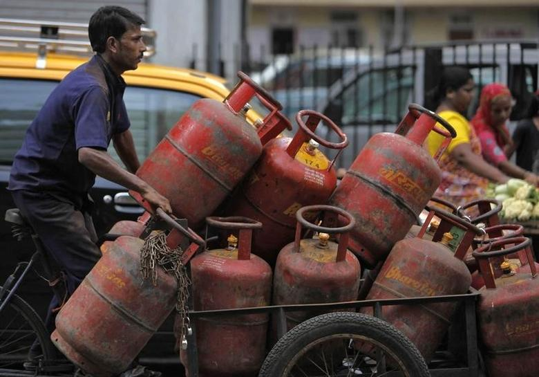 An employee of a cooking gas agency transports gas cylinders on a cart in Mumbai June 7, 2010. REUTERS/Danish Siddiqui/Files