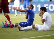 El uruguayo Luis Suarez (D) se agarra los dientes después de morder al italiano Giorgo Chiellini (I) durante el enfrentamiento entre los dos equipos por la disputa de la clasificación a los octavos de final de la Copa del Mundo 2014 en el Arena Dunas, en Natal, 25 de junio de 2014. La marca de póker 888 dijo que estaba revisando su acuerdo de patrocinio con el delantero uruguayo Luis Suárez después de que el futbolista fue acusado de morder a un rival durante un partido del Mundial contra Italia. REUTERS/Tony Gentile