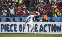 Игрок сборной Аргентины Лионель Месси радуется голу, забитому в ворота сборной Нигерии в матче чемпионата мира в Порту-Алегри 25 июня 2014 года. Дубль Лионеля Месси принес сборной Аргентины третью кряду победу на чемпионате мира в Бразилии, обеспечив ей первое место в группе F и путевку в 1/8 финала. REUTERS/Edgard Garrido