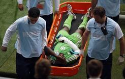 Jogador da Nigéria Michael Babatunde é carregado para fora de campo em partida contra a Argentina, no Estádio Beira-Rio, em Porto Alegre. 25/6/2014 REUTERS/Marko Djurica