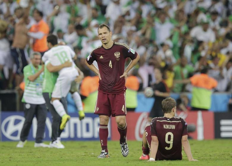 Russia's Sergey Ignashevich (L) and teammate Alexander Kokorin react as they walk off the field after the match against Algeria at the 2014 World Cup Group H soccer match at the Baixada arena in Curitiba June 26, 2014.   REUTERS/Henry Romero