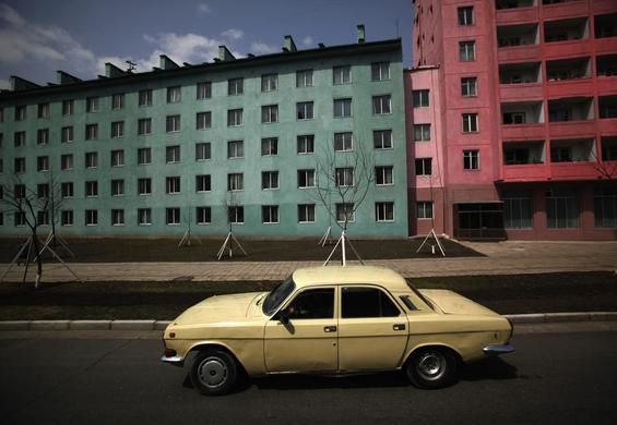 A car drives past residential buildings in Pyongyang, April 11, 2012.   REUTERS-Bobby Yip