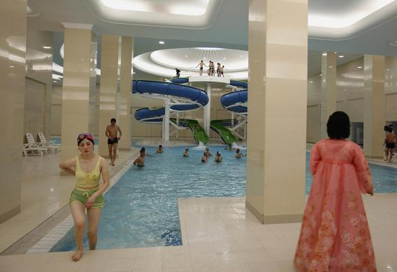 A woman in traditional Korean costume watches as a student leaves a swimming pool of Kim Il-sung University in Pyongyang, April 11, 2012.   REUTERS-Bobby Yip