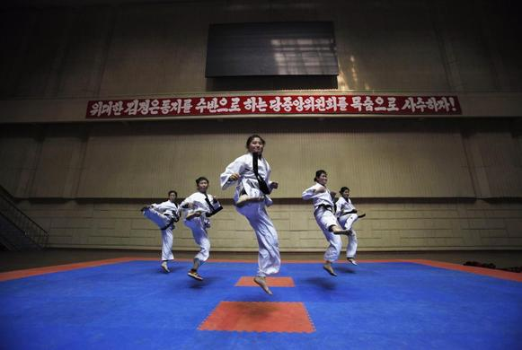 Girls train in a Taekwondo Hall in Pyongyang April 12, 2012. The banner at background reads 'Let us defend the Party Central Committee headed by the respected comrade Kim Jong-un, at the cost of our lives!' REUTERS-Bobby Yip