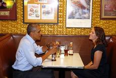 U.S. President Barack Obama visits with Rebekah Erler at Matt's Bar, after receiving a letter from her explaining what it is like living in her shoes, in Minneapolis, Minnesota June 26, 2014.   REUTERS/Larry Downing
