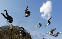 Люди катаются на карусели в Парке Горького 24 июня 2007 года.  Выходные в Москве начнутся прохладной субботой, но к воскресенью в столице вновь станет по-летнему тепло, ожидают синоптики. REUTERS/Oksana Yushko