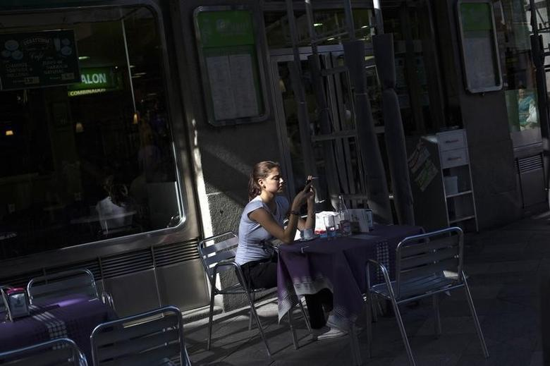 A woman checks her mobile phone in a nearly empty bar at a shopping district in Madrid July 30, 2012.  REUTERS/Susana Vera