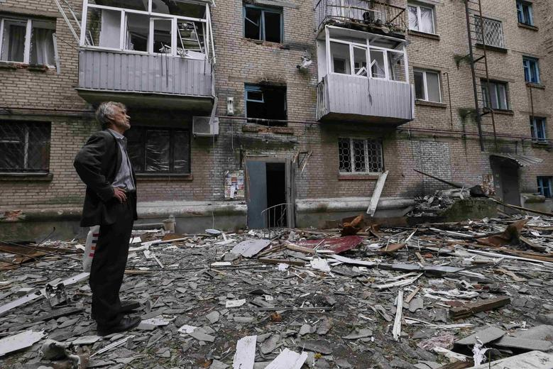 A man looks at a residential building, where he resides, which was damaged by what locals say was overnight shelling by Ukrainian forces, in the eastern Ukrainian town of Slaviansk June 12, 2014. REUTERS/Gleb Garanich