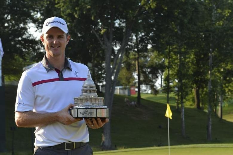 Jun 29, 2014; Bethesda, MD, USA; Justin Rose holds the Quicken Loans National trophy up after defeating Shawn Stephani in a one-hole playoff on the 18th green after the Quicken Loans National golf tournament at Congressional Country Club - Blue Course. REUTERS/Tommy Gilligan-USA TODAY