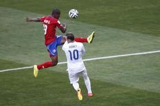 Zagueiro da Costa Rica Roy Miller (vermelho) chuta bola em dividida com Wayne Rooney, da Inglaterra, em partida em Belo Horizonte. 24/6/2014 REUTERS/Leonhard Foeger