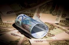 Купюры валют евро и рубль в Москве 17 февраля 2014 года. Рубль падает в первую торговую сессию июля на фоне завершения перемирия на Украине и российского налогового периода, что провоцирует бегство от риска и снижение предложения валюты от экспортеров на внутреннем рынке. REUTERS/Maxim Shemetov