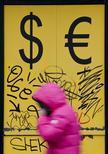 Пешеход проходит мимо пункта обмена валюты в Москве 3 марта 2014 года. Рубль незначительно подорожал в начале биржевой сессии среды после существенного падения накануне из-за возобновления боевых действий на Украине и снижения продаж экспортной выручки в начале месяца. REUTERS/Maxim Shemetov