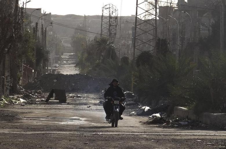 Men ride a motorbike along a deserted street filled with debris in Deir al-Zor, eastern Syria March 7, 2014. Picture taken March 7, 2014. REUTERS/Mohamed al-Khalif