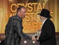 Singer Garth Brooks (L) presents the Crystal Milestone Award to Merle Haggard at the 49th Annual Academy of Country Music Awards in Las Vegas, Nevada April 6, 2014.    REUTERS/Robert Galbraith