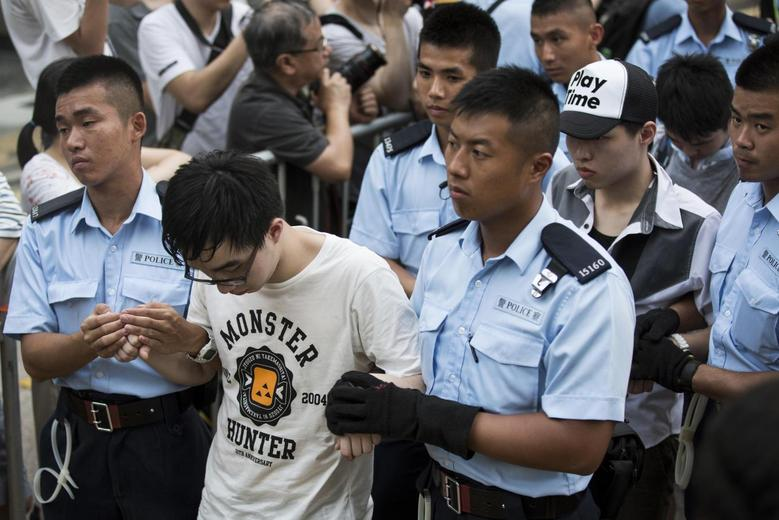 Protesters are taken away by police officers after staying overnight at Hong Kong's financial Central district July 2, 2014. REUTERS/Tyrone Siu