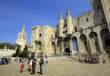 Visitors walk outside the Palais des Papes (Palace of the Popes) in Avignon, the site of France's biggest summer festival,  April 19, 2011.    REUTERS/Jean-Paul Pelissier