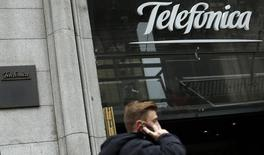 A man talks on a mobile phone as he walks past Spanish telecom group Telefonica flagship store in central Madrid November 8, 2013.   REUTERS/Sergio Perez