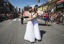 A newly wed couple kisses in their wedding dresses during the gay pride parade in Toronto, June 30, 2013.    REUTERS/Mark Blinch