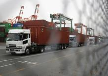 Trucks line up after they loaded containers at a port in Tokyo March 19, 2014. REUTERS/Yuya Shino
