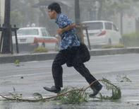 Мужчина переходит дорогу в городе Наха на острове Окинава 8 июля 2014 года. Ливневые дожди, принесенные ослабевшим, но все еще опасным тайфуном, обрушились в среду на японский остров Окинава, привели там к гибели двух человек и грозят стране наводнениями по мере того, как шторм направляется к основным островам. REUTERS/Kyodo