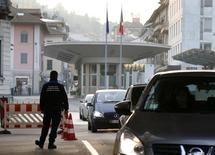 A Swiss customs officer checks vehicles at the Swiss-Italian border with Como in Chiasso, in the canton of Ticino March 14, 2014.  REUTERS/Denis Balibouse