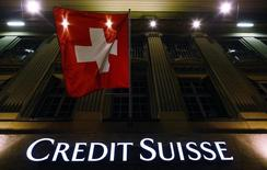 The logo of Swiss bank Credit Suisse is seen below the Swiss national flag at a building in the Federal Square in Bern May 15, 2014. REUTERS/Ruben Sprich