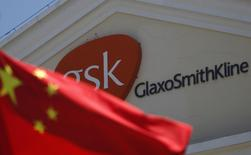 A Chinese national flag is seen in front of a GlaxoSmithKline office building in Shanghai in this July 12, 2013 file photo.  REUTERS/Aly Song