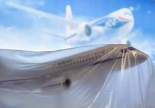 A Russian Sukhoi Superjet SSJ-100 model aircraft sits under plastic sheeting at the 2014 Farnborough Airshow in Farnborough, southern England July 13, 2014. Britain has delivered a calculated diplomatic snub to Russia by failing to invite any of its government officials to next week's Farnborough Airshow in protest over Moscow's actions in Ukraine. The Farnborough International Airshow (FIA), which runs from July 14-20, is a major event in the aviation calendar to which Russia usually sends a large contingent in the search for foreign sales REUTERS/Kieran Doherty (BRITAIN - Tags: TRANSPORT BUSINESS POLITICS)