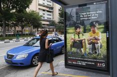A woman walks past a World Cup anti-gambling advertisement at a taxi stand in Singapore July 9, 2014.  REUTERS/Edgar Su