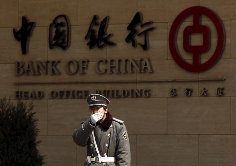 A security guard covers his mouth as he yawns while standing guard outside the headquarters of the Bank of China in the financial district of Beijing March 23, 2010.  REUTERS/David Gray