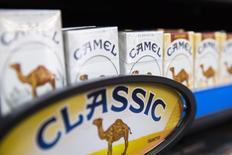 Пачки сигарет Camel на полке табачной лавки в Нью-Йорке 11 июля 2014 года. Производитель сигарет Camel американская компания Reynolds American Inc купит конкурента Lorillard Inc за $27,4 миллиарда, включая долги, расплатившись деньгами и акциями. REUTERS/Lucas Jackson