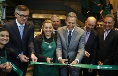 CEO of Starbucks Howard Schultz (front 3rd R) inaugurates the coffee chain's first Colombian store at 93 park in Bogota July 16, 2014. REUTERS/John Vizcaino