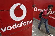 En la imagen, un hombre habla por teléfono entre logos de Vodafone en Calcuta, el 20 de mayo de  2014. La británica Vodafone dijo que es poco probable que se interese por los activos en telecomunicaciones que serán vendidos en México por América Móvil, dado que la operación no estaría en línea con su enfoque en el mercado corporativo. REUTERS/Rupak De Chowdhuri
