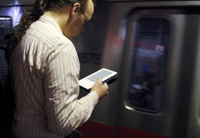 7月18日、アマゾンは電子書籍コンテンツを月額9.99ドルで無制限に提供するサービスを発表した。写真は電子書籍を読む通勤客。マサチューセッツ州の地下鉄で2011年3月撮影(2014年 ロイター/Brian Snyder)