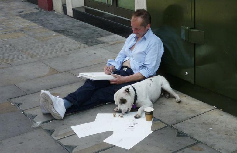 John Dolan sits on a street sketching alongside his dog George as he poses for a photograph in London, July 17, 2014. REUTERS/Daan Kaur