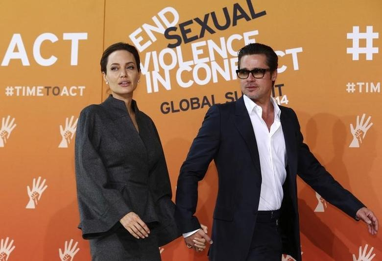 Angelina Jolie and Brad Pitt arrive at the Excel centre in London June 13, 2014. REUTERS/Luke MacGregor