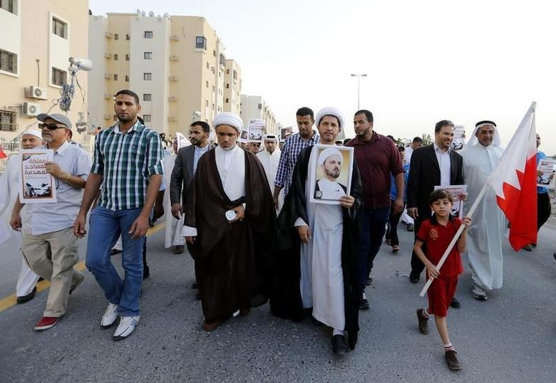 General Secretary of Bahrain's main opposition party Al Wefaq, Sheikh Ali Salman holding a banner with photo of Shi'ite scholar, Sheikh Hasan Najaty, who was stripped off his Bahraini nationality last year and is being deported, marches during an anti-government protest in Al A'ali  south of Manama, April 18, 2014.  REUTERS/Hamad I Mohammed