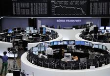 Traders are pictured at their desks in front of the DAX board at the Frankfurt stock exchange July 25, 2014.      REUTERS/Remote/Janine Eggert