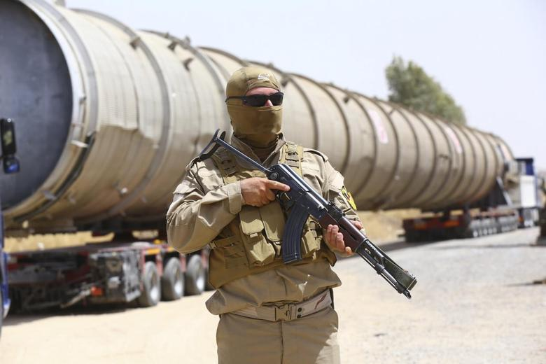 A member of the Kurdish security forces takes up position with his weapon as he guards a section of an oil refinery, which is being brought on a truck to Kalak refinery in the outskirts of Arbil, in Iraq's Kurdistan region, July 14, 2014. REUTERS/Stringer