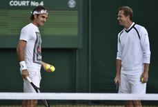 Roger Federer of Switzerland (L) speaks with his coach Stefan Edberg during a practice session at the Wimbledon Tennis Championships in London July 5, 2014.         REUTERS/Toby Melville