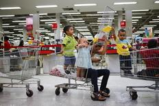 A customer uses a mobile phone while sitting inside a shopping trolley next to children at a state-run Bicentenario supermarket in Caracas May 2, 2014. REUTERS/Jorge Silva