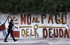 """Женщина профходит мимо граффити """"Нет - платежам по долгам"""" в Буэнос-Айресе 28 июля 2014 года. Аргентина объявит дефолт по долгам в течение нескольких часов, поскольку переговоры с кредиторами-""""отказниками"""" в среду провалились.   REUTERS/Marcos Brindicci"""