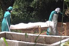 Медицинские работники переносят тело жертвы лихорадки Эбола в Кенеме, Сьерра-Леоне 25 июня 2014 года. Сьерра-Леоне ввела режим чрезвычайного положения из-за унесшей уже 729 жизней в Западной Африке вспышки лихорадки Эбола, очаги распространения которой теперь будут переведены в карантин, за которым будет следить армия. REUTERS/Umaru Fofana