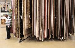 A man stands near a display of carpets while shopping at a Home Depot store in New York in this file image from December 23, 2009.   REUTERS/Lucas Jackson