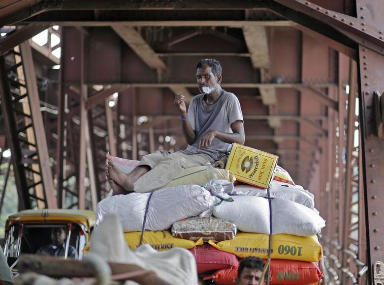 A worker smokes while sitting on a cart carrying rice sacks in New Delhi August 1, 2014. REUTERS/Anindito Mukherjee